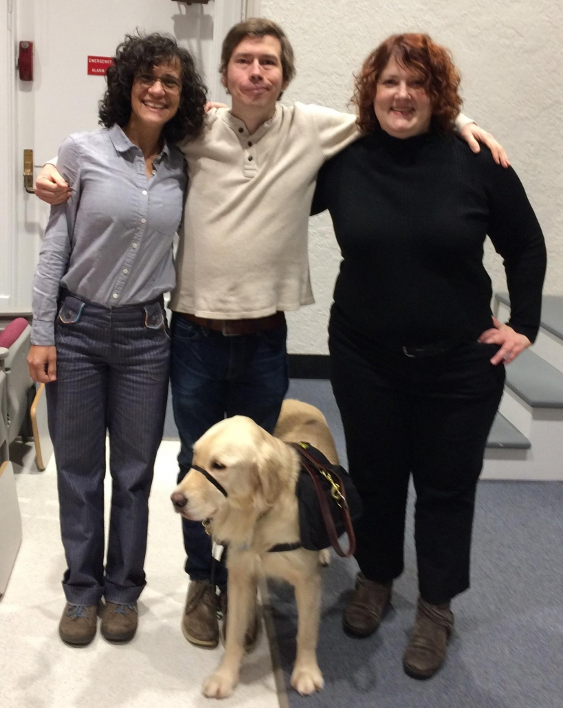 """Who Am I To Stop It"" Producer Cheryl Green & Cynthia Lopez, with star Brandon Michael Scarth and his service dog stand upright and smile into the camera. Brandon, a man with short, blond hair is in the middle with his arms around Cheryl, who has curly, long brown hair and glasses, and on the other side is Cynthia, who has red-brown, curly, shoulder-length hair."
