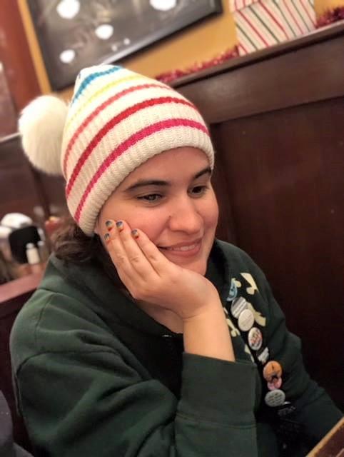 Caitlin sitzt mit ihrem Gesicht auf ihrer Handfläche ruhend an einem Tisch. Sie trägt eine regenbogenfarbigen Beanie und hat regenbogenfarbene Fingernägel. Sie lächelt und blickt leicht nach unten.