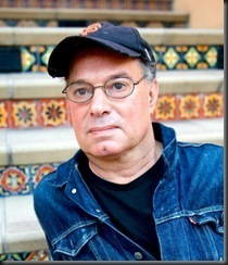 A man with a black cap and glasses sits on stairs