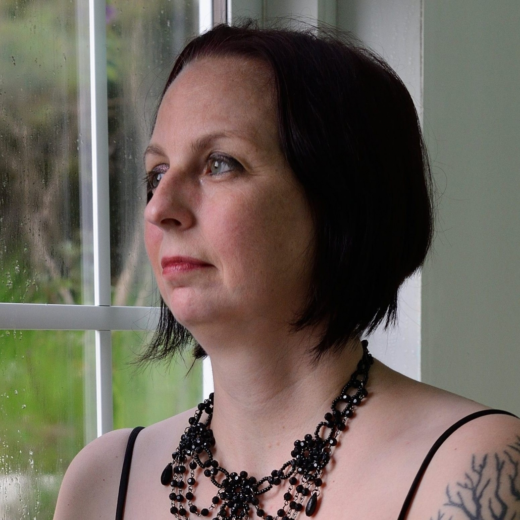 A woman with short, black, chin-long hair and a black necklace is looking out the window.