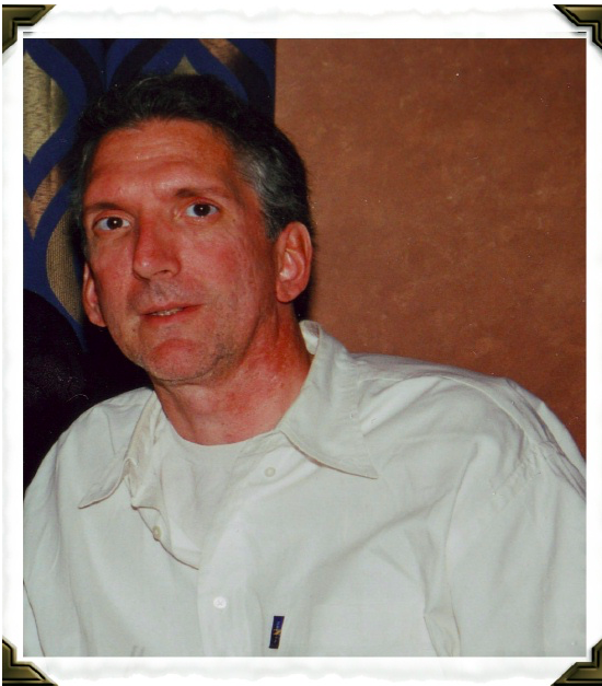 Image of a man with blackish/grey short hair and a white sweater.