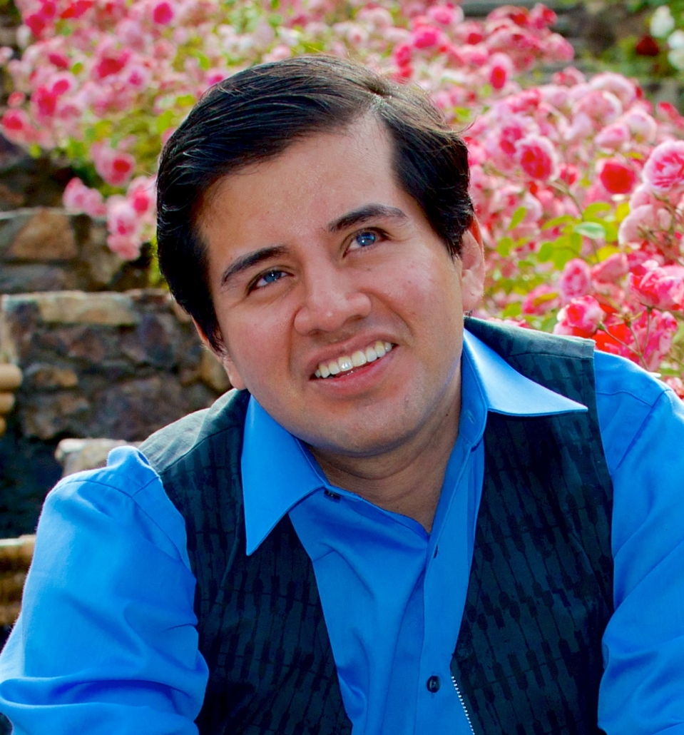 Belo Cipriani: A man with short, brown hair wearing a blue shirt is sitting on stairs with pink flowers in the background. He looks into the distance and is smiling.