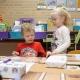 """Lucas und Lotte, zwei Kinder, sind in ihrem Klassenzimmer und spielen an einem Tisch. Lucas hat kurze blonde Haare und trägt ein rotes """"Cars"""" Shirt. Lotte hat blonde, lange Haare und trägt ein weißes Shirt."""