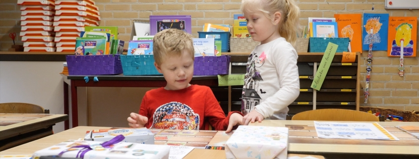 "Lucas and Lotte, two young children, are in their classroom playing on a table. Lucas has blonde hair and wears a red ""car"" shirt, and Lotte has blonde, long hair bound to a ponytail and wears a white shirt."