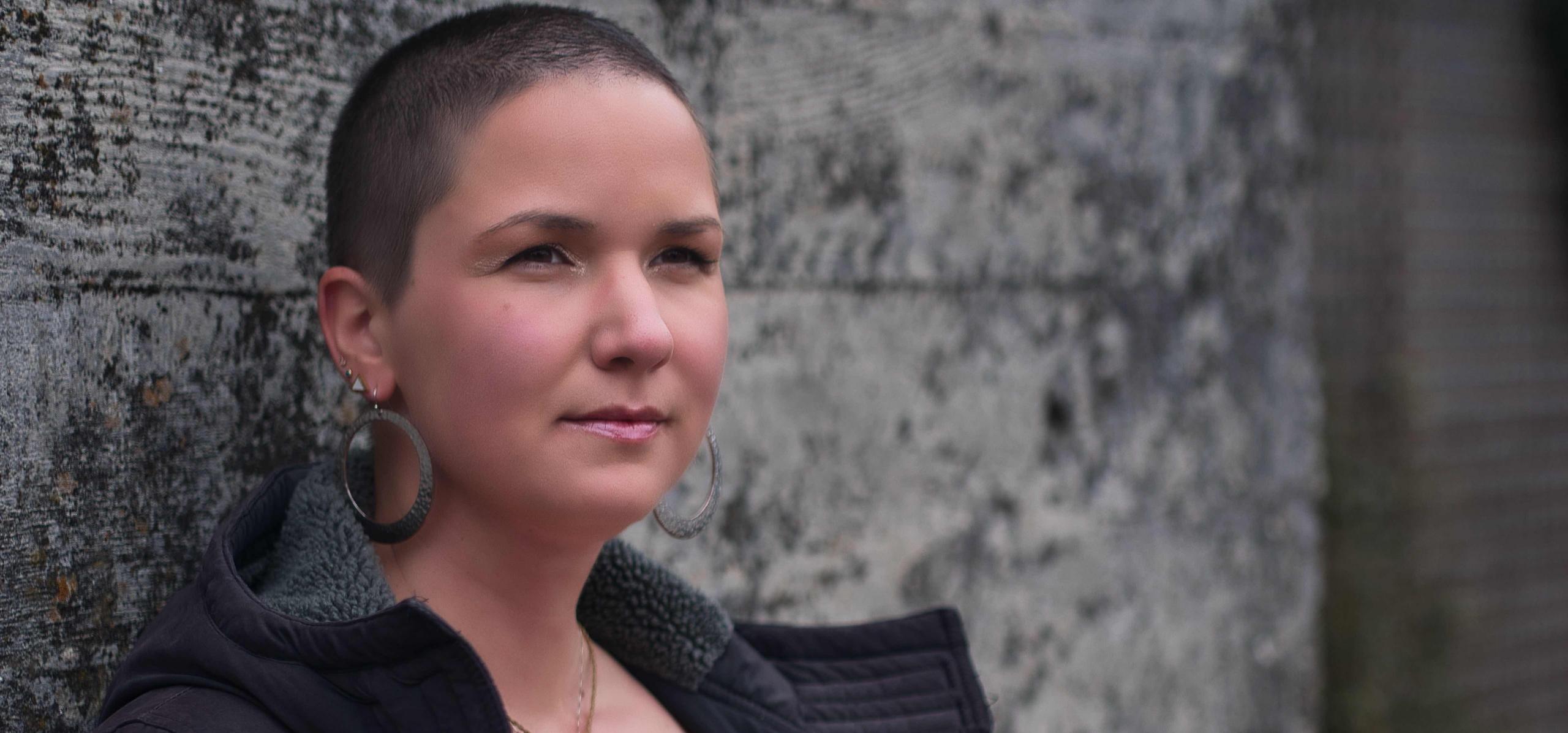 Karina, eine Frau mit rasierten, braunen Haaren steht an einer grauen Wand. Sie trägt große, runde Ohrringe.