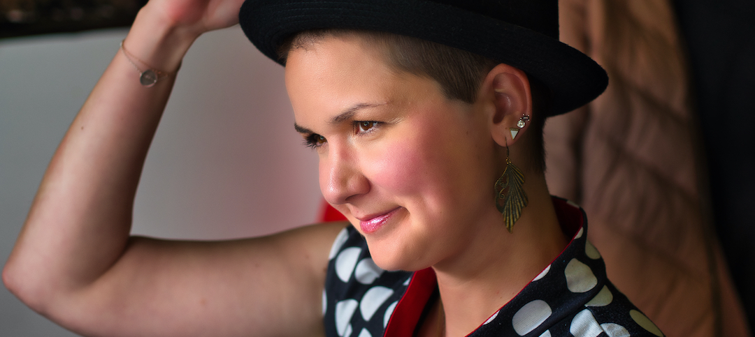 Karina, a woman with super short brown hair is wearing a black hat and has her hand on top of the hat to take it off. She wears huge, feather-like earrings and lipstick.