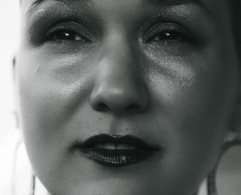 Schwarz-weiß Foto von Karina, einer Frau mit rasierten Haaren. Sie trägt Glitzerlidschaften und roten Lippenstift.