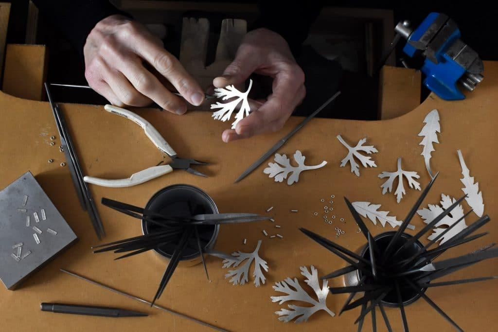 Nya handgjorda silversmycken tillverkas vid arbetsbänken.