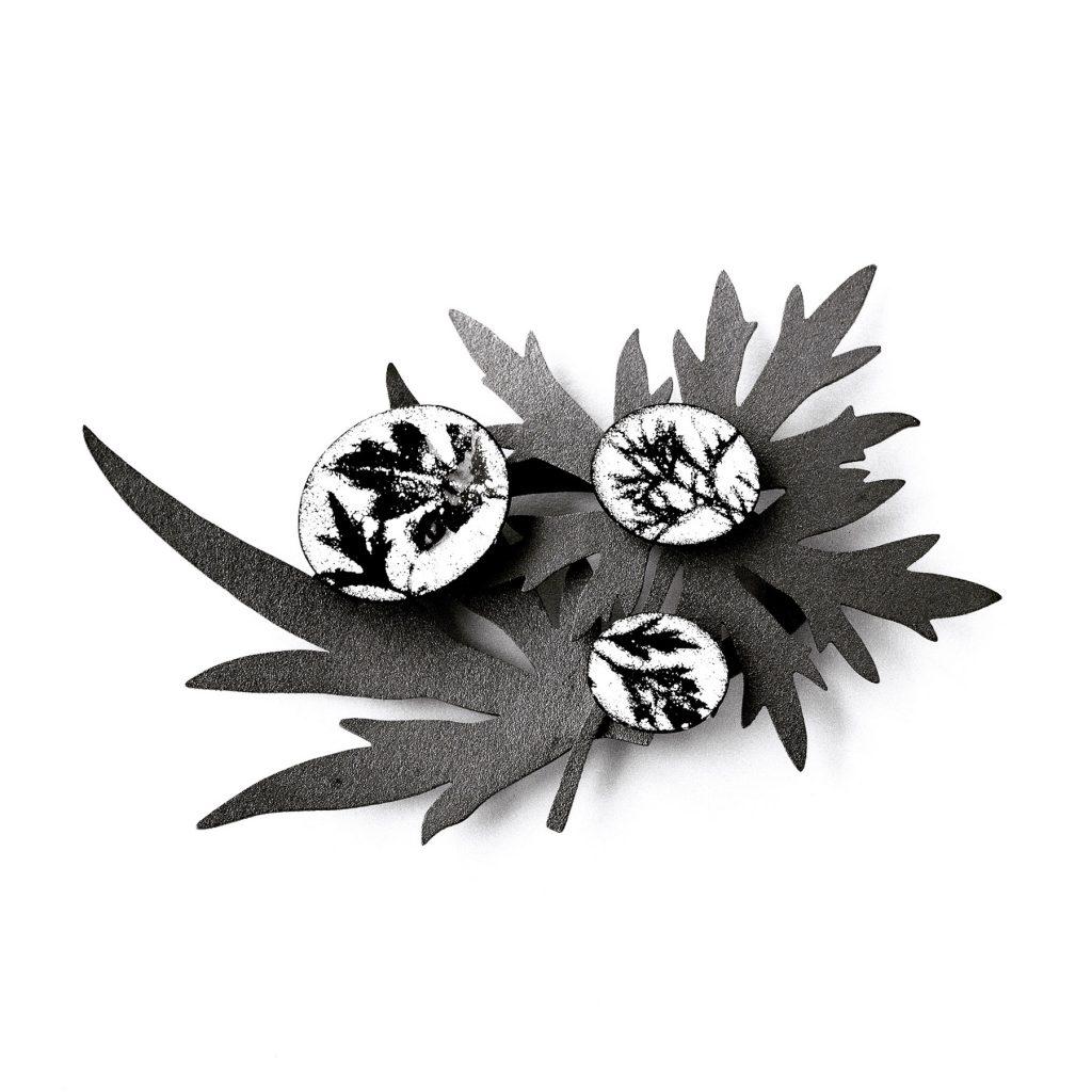 Brosch av svartoxiderat silver och emalj. Broschen består av två stora löv av svart silver och tre små emaljer med motiv av små svarta löv på vit botten.