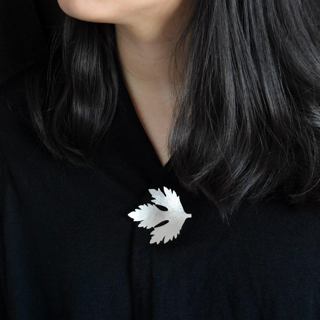 En liten silverbrosch i form av ett persiljeblad.