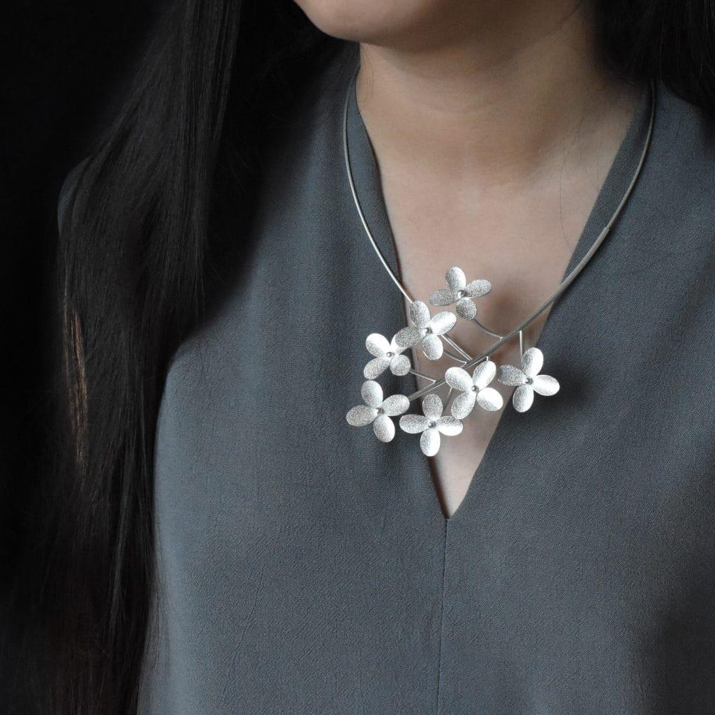 Halssmycke av silver med sju blommor