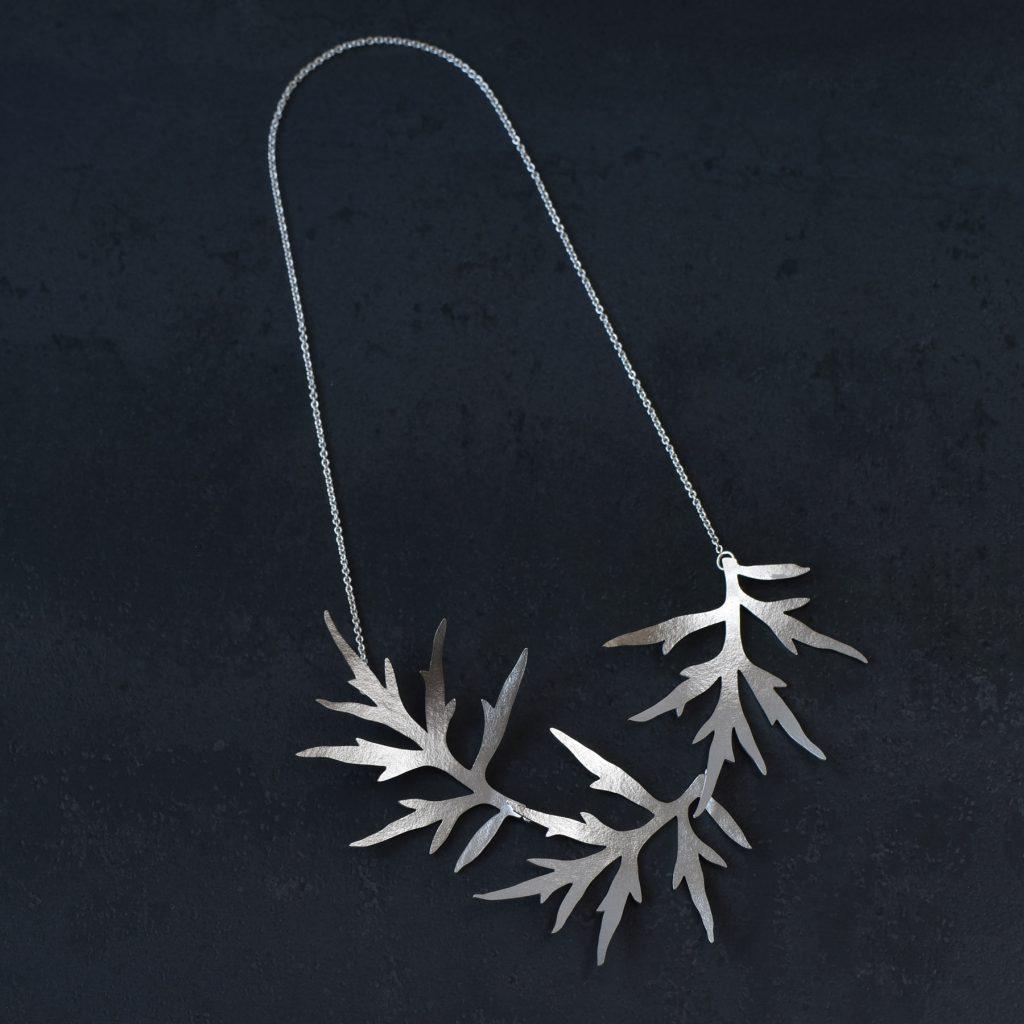 Halssmycke av silver med tre gråboblad i rad på kedja. Låset sitter under det yttersta bladet.