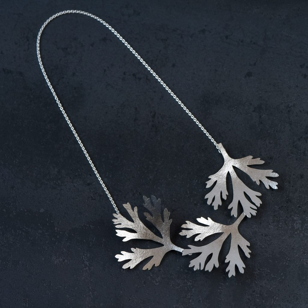 Halssmycke av silver med tre blad av nunneört på rad. Bladen är fästa i en kedja och låset sitter bakom det yttersta bladet.