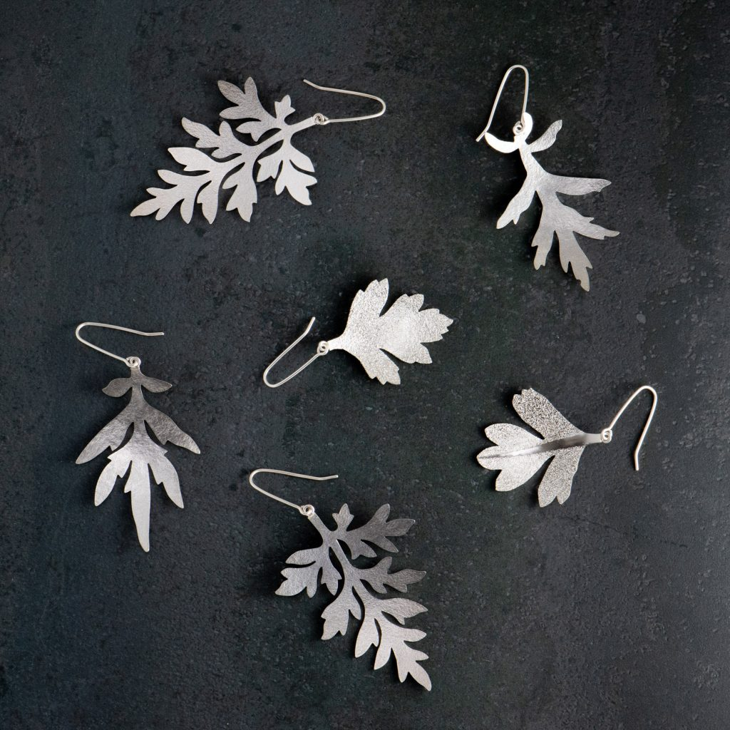 Olika varianter av bladörhängen. Gråbo, Malörtsambrosia och Hagtorn. Tillverkade av silver.