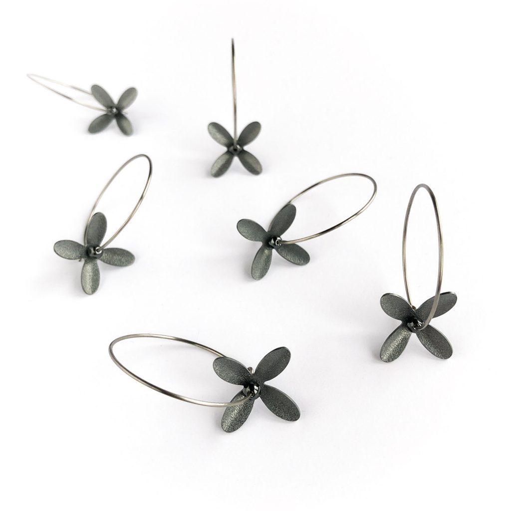 Örhängen med svarta blommor på ring. Örhängena är tillverkade av titan, svartoxiderat silver och hematit.