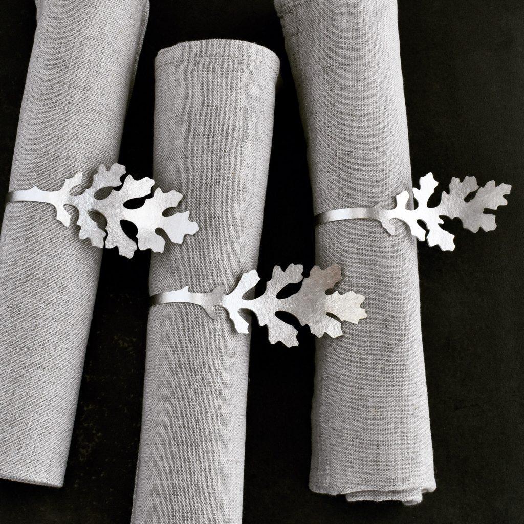 Handgjorda servettringar av silver med korsörtsblad.