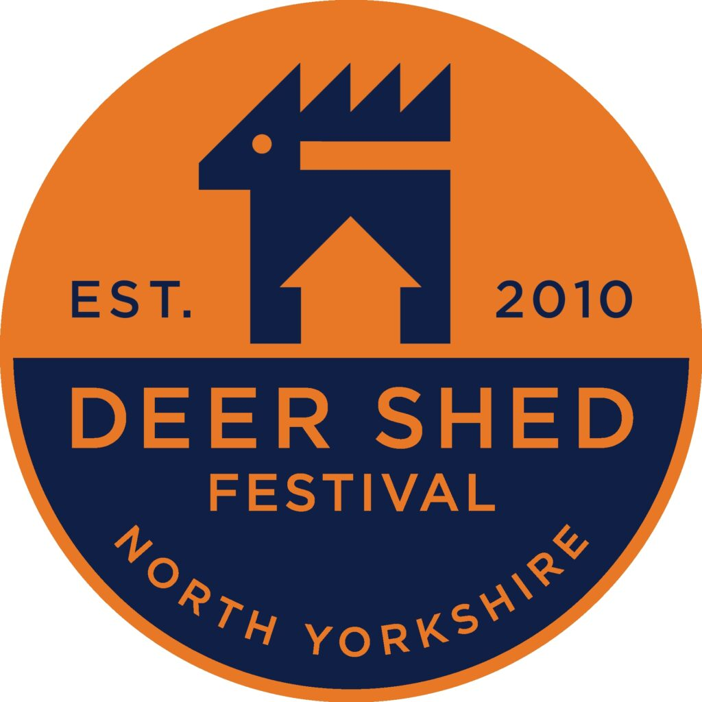 It's the Deer Shed Festival logo, featuring some really cool graphics of a deer with a shed outline between where it's legs are (I've not done very well at describing that, I'm so sorry), and then the text says Deer Shed Festival / Est. 2010 / North Yorkshire. In a bright orange and indigo colour scheme.
