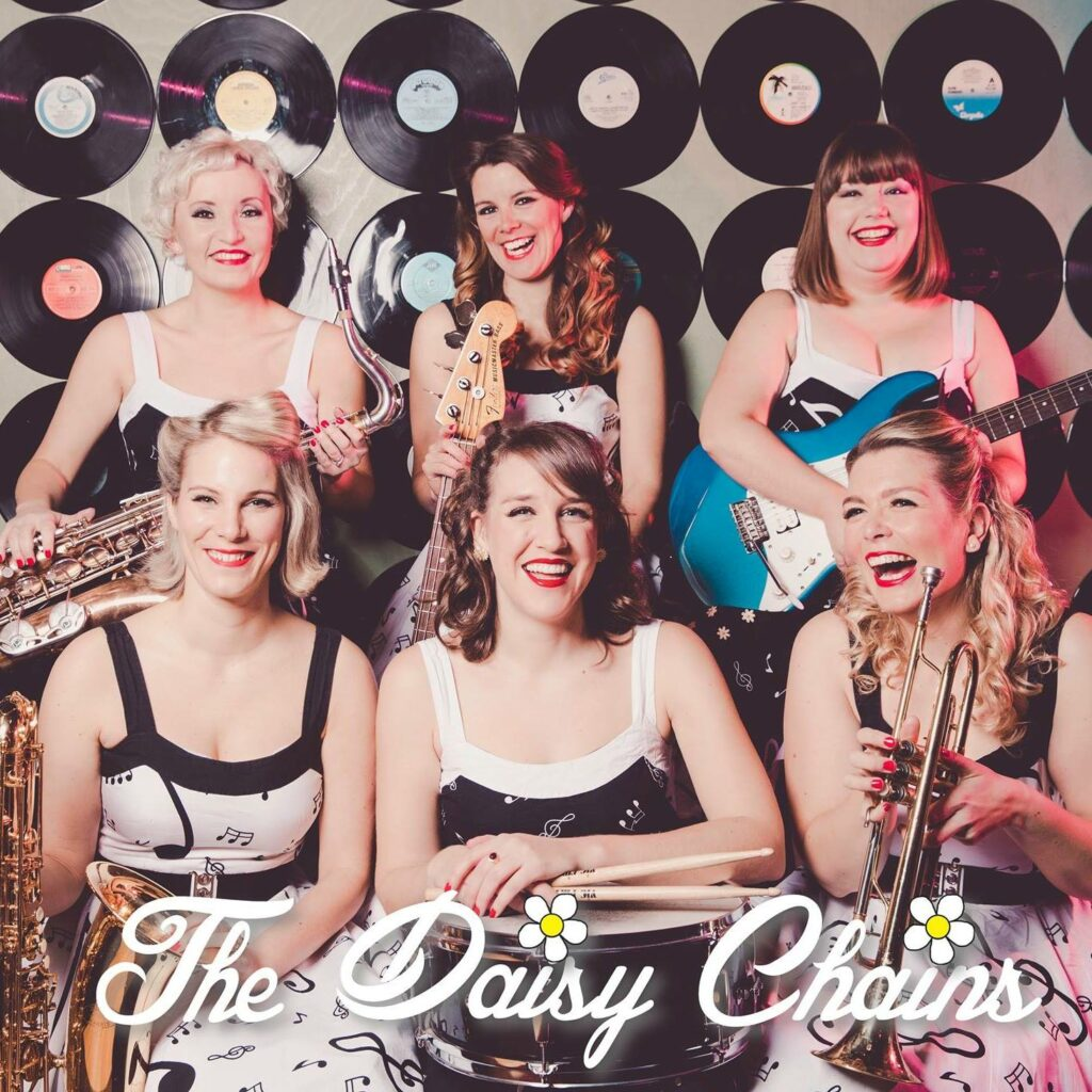 It's The Daisy Chains image, featuring 6 of us hanging out in front of a wall decorated with vinyl records holding our instruments and laughing.