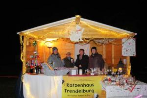 Verkaufsstand des Vereins am Abend, mit Beleuchtung, vier Personen