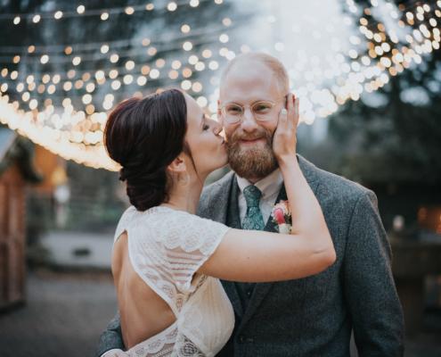 Brautpaar bei einer Winterhochzeit mit Lichterketten im Hintergrund