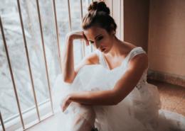 Braut sitzt vor Fenster und blickt nach unten