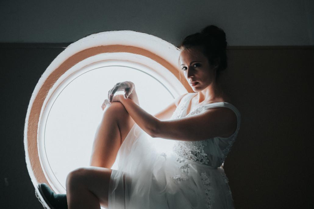 Braut sitzt vor Fenster