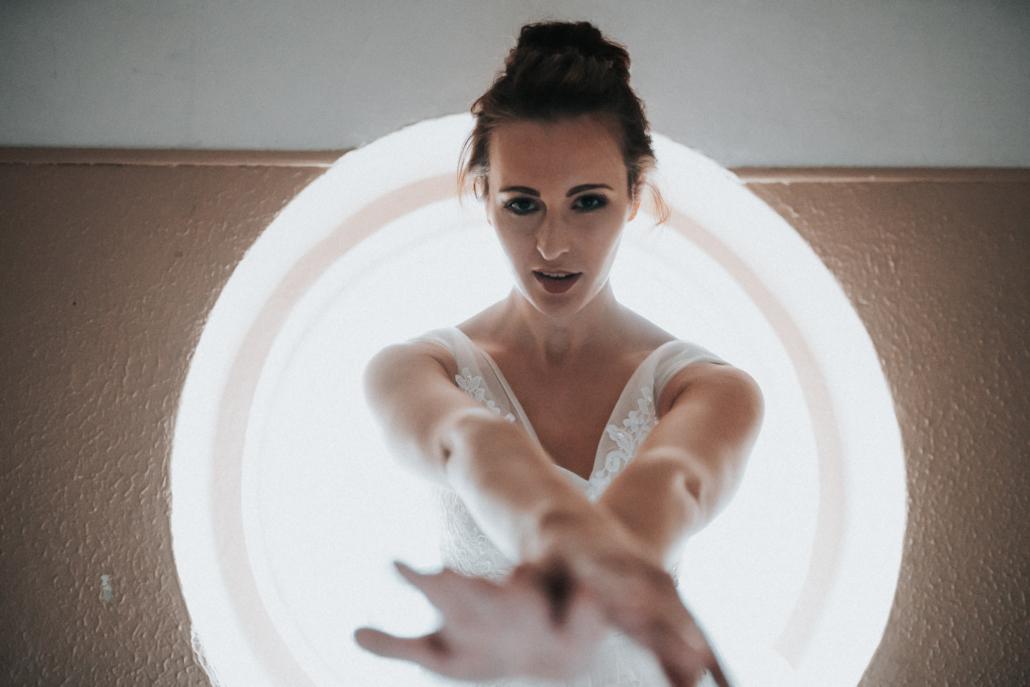 Frau in Brautkleid vor Fenster