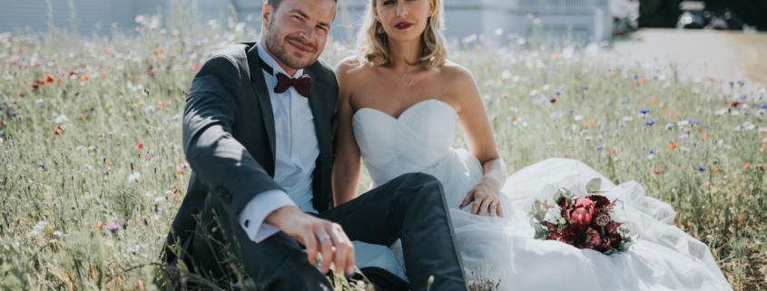 Brautpaar sitzt am Hochzeitstag in einer Wiese