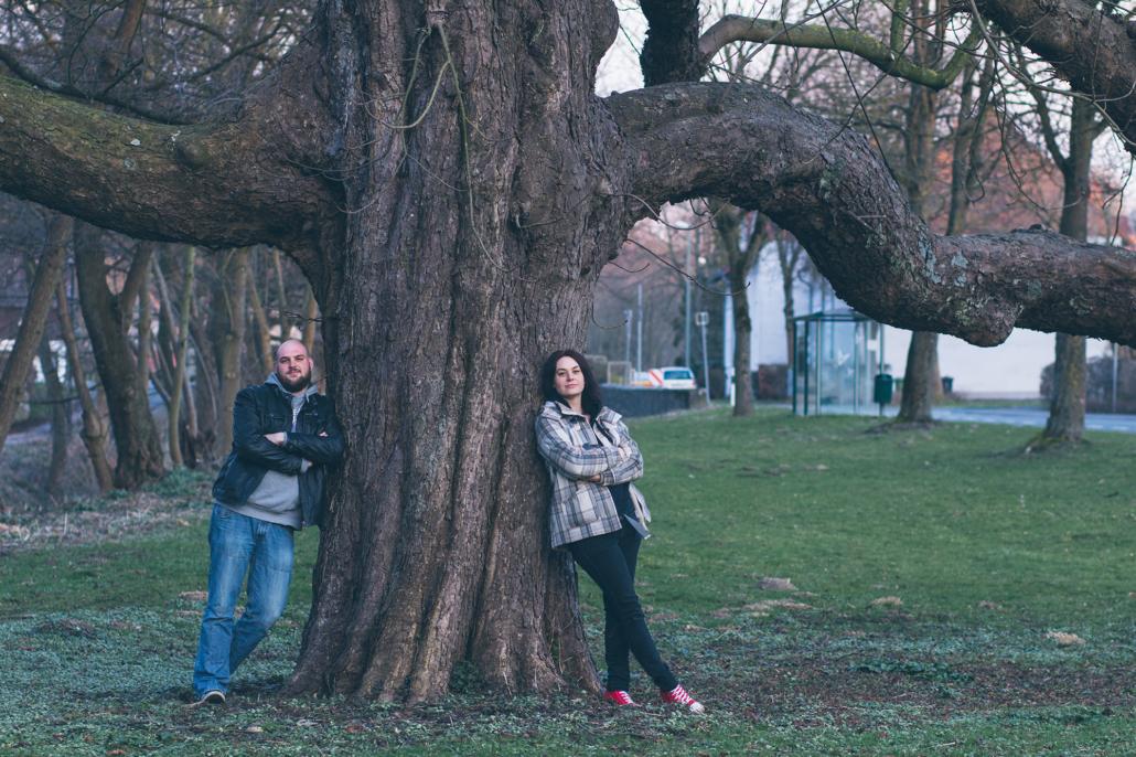ein paar lehnt gemeinsam an einem Baum