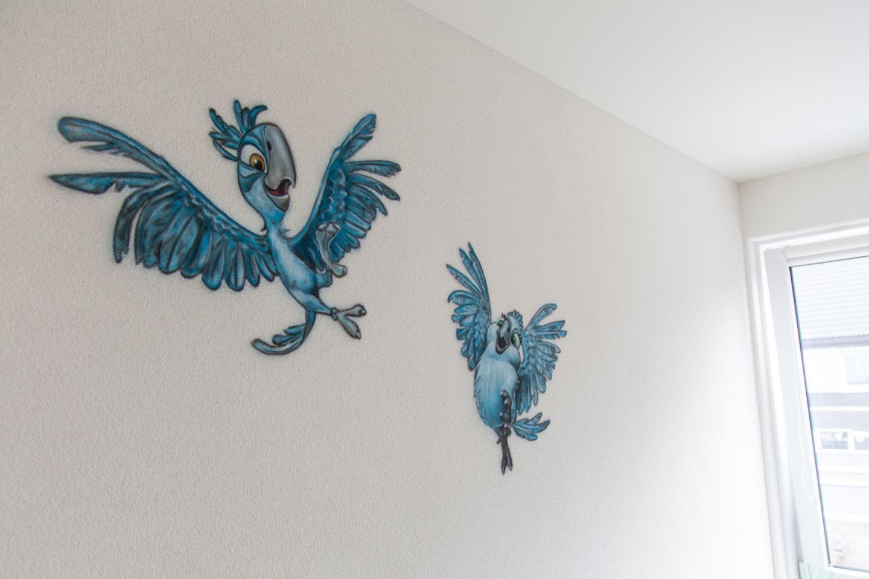 Muurschildering van blauwe vogels uit de animatiefilm Rio
