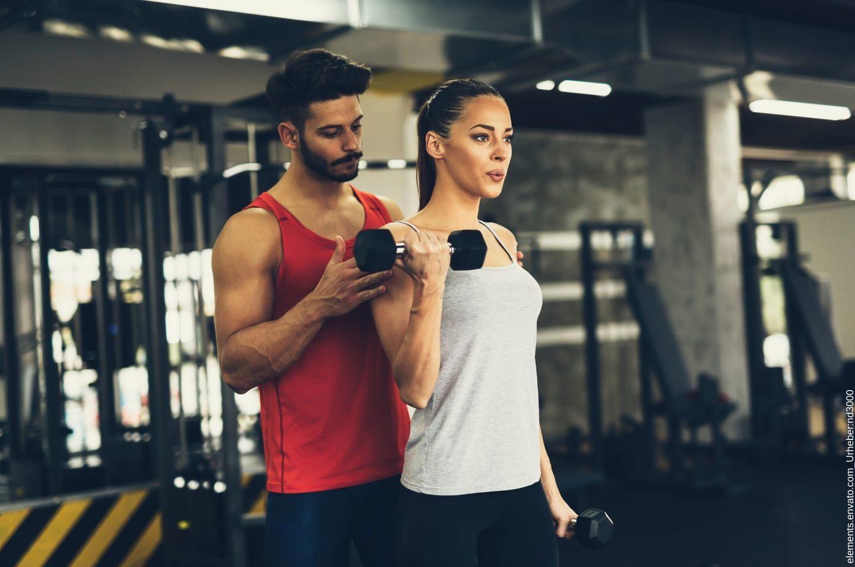 Personal Trainer betreut eine Frau für die er einen Trainingsplan erstellt hat.
