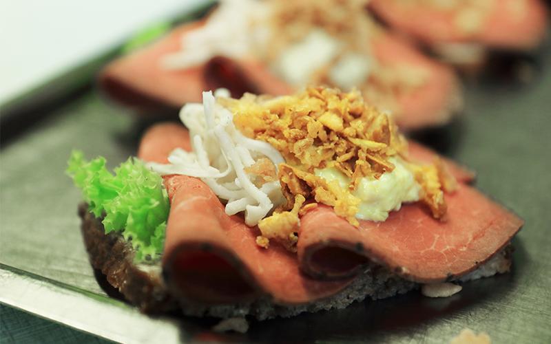 Knabstrup Hallens smørrebrødsmadder fra caféen, roastbeef med grøn salat, ristedeløg, remulade og pebberrod