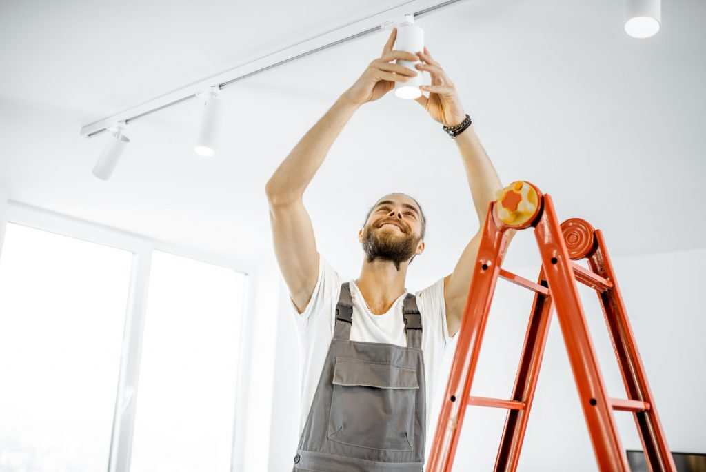 Electrician installing light at home
