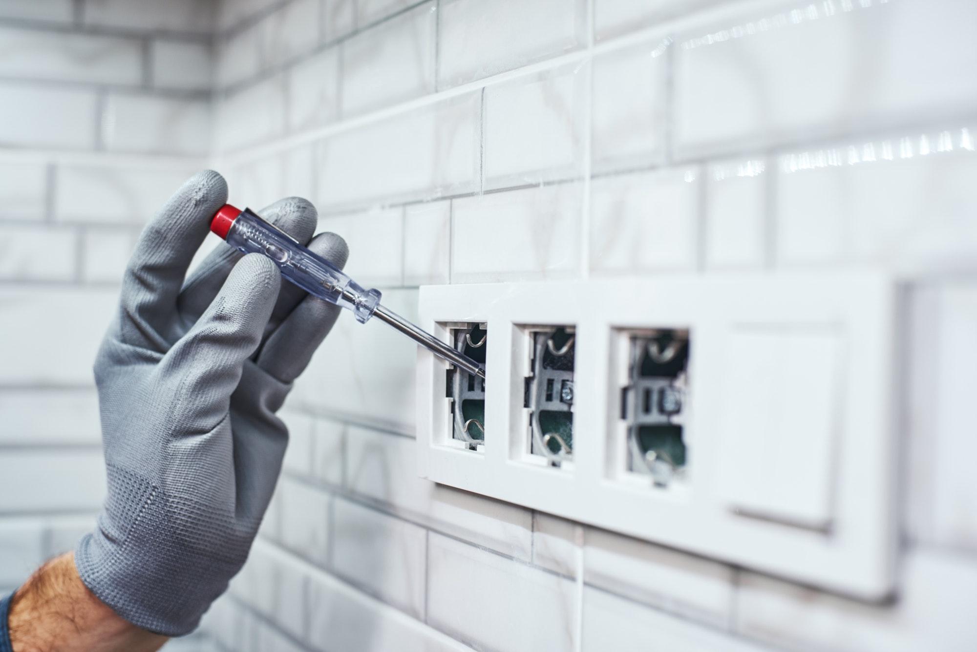Electrical network measurement. Close-up of senior handyman setting new sockets