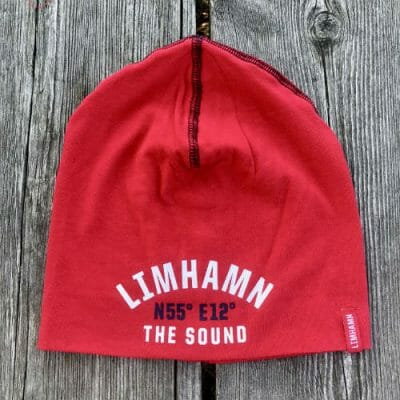 Röd Limhamnsmössa med longitud och latitud för Limhamn samt The Sound från Kokkolit på Limhamn
