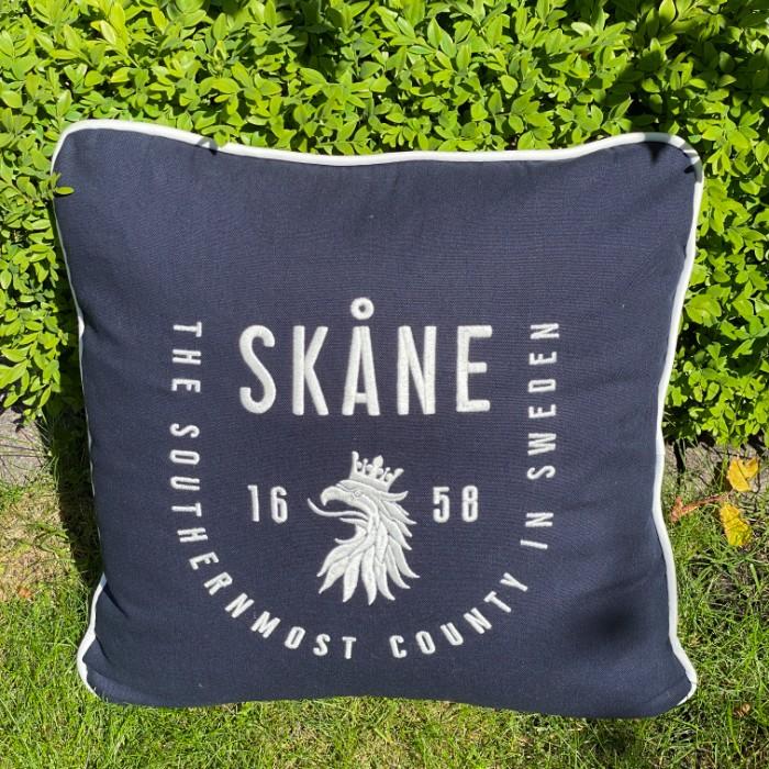 En bänk med två ljusa kuddar från Kokkolit med Limhamns motiv sillar och Sillatåg