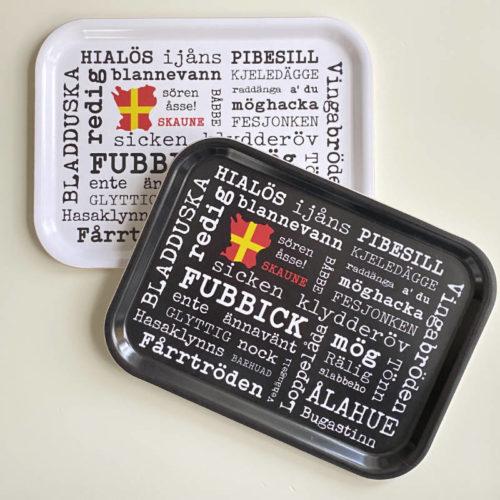 Två frukostbrickor, svart och vit, med skånska ord från Kokkolit