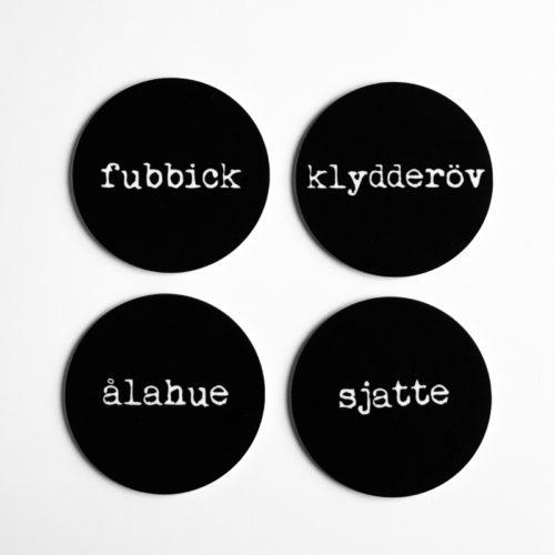 fyra glasunderlägg i svart med skånska ord fubbick ålahue klydderöv sjatte