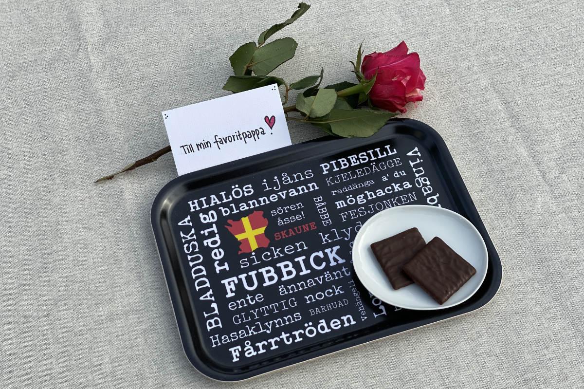 """Svart frukostbricka med skånska ord i vit text. Ovanför brickan ligger en röd ros och ett kort där det står """"Till min favoritpappa"""""""