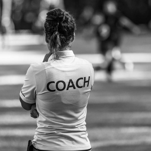 Back view of a female sport coach watching her team compete at an outdoor football field