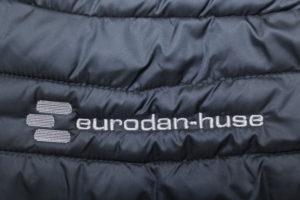 Broderi af logo på tøj - her Eurodan huse logo i lamel på dynejakke.