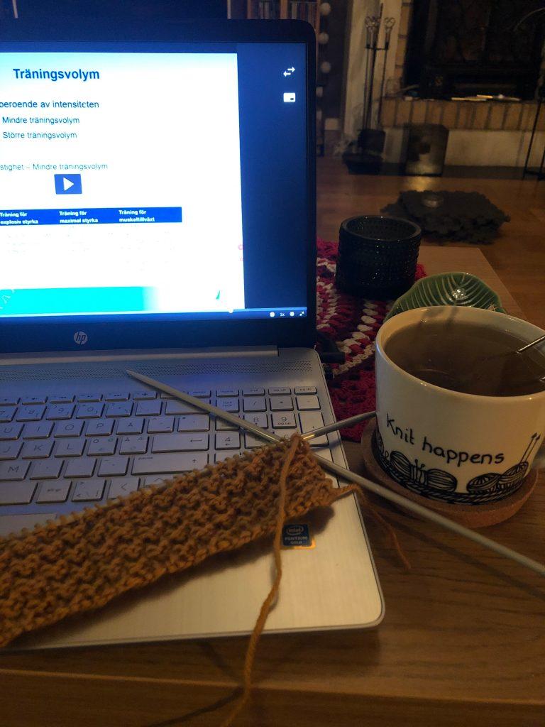 """En bild på min laptop där jag tittar på en föreläsningsfilm om träningslära, min stickning (senapsgul ruta) och en tekopp med texten """"knit happens""""."""