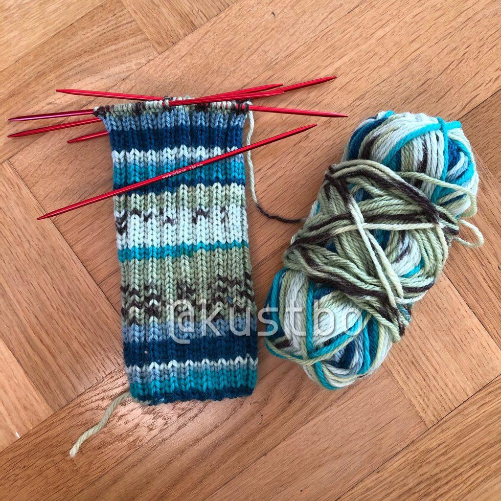 En påbörjad stickad socka och ett halvt nystan blå-grönt garn