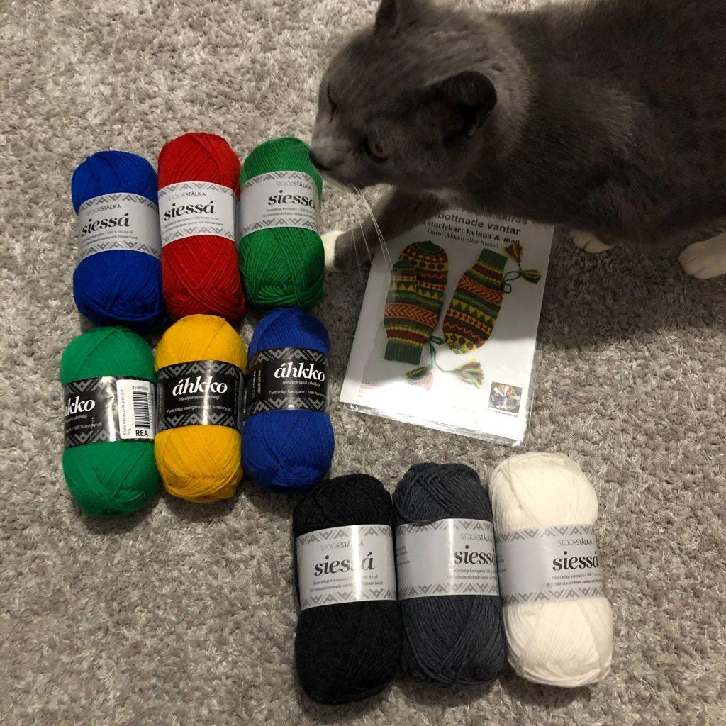 Bild på 9 garnnystan i olika färger (áhkko och siessá), en stickbeskrivning (vantar) och en katt =)