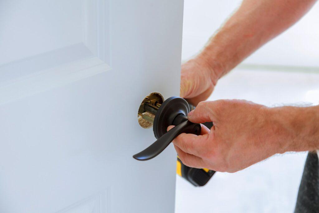 carpenter Installing the lock on the door Installation of the door lock.