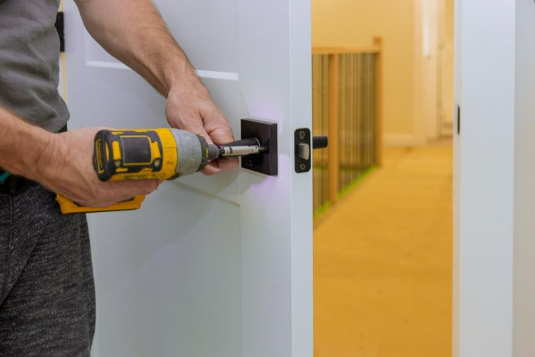 Handyman installing the door lock in the room with screwdriver