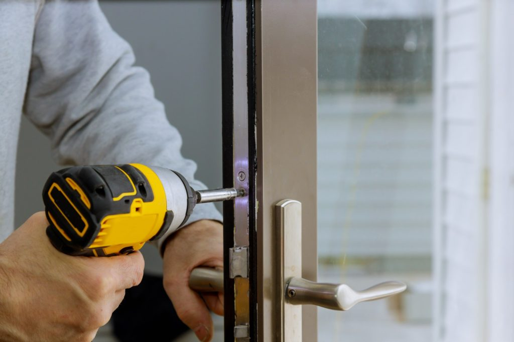 Locksmith in installing new house door lock hand holds the screwdriver