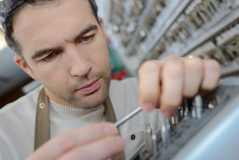 man in apron making duplicates of keys