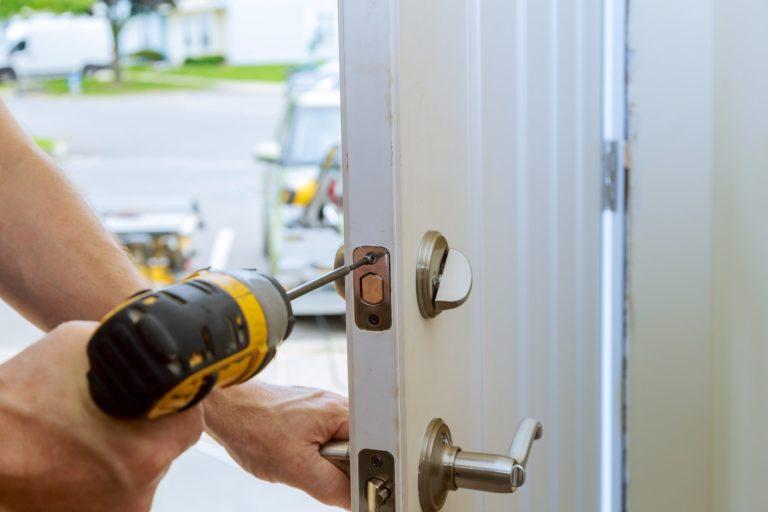 worker's hands installing new door locker man repairing the doorknob. closeup