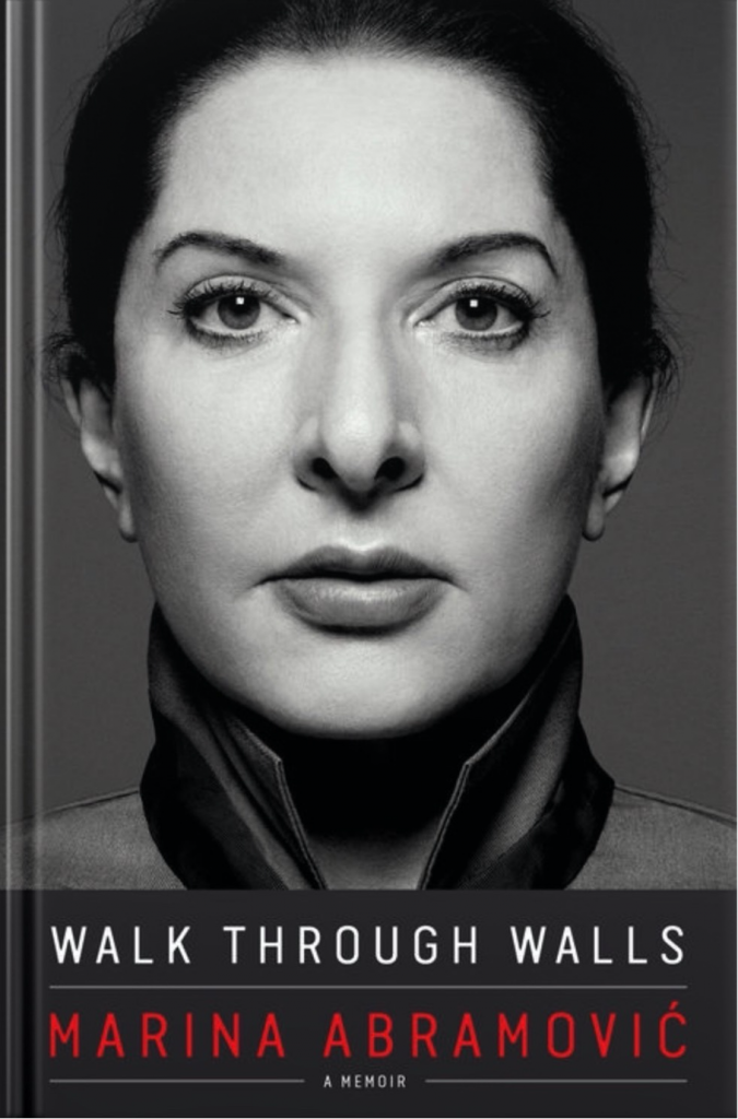 "Cover of Marina Abramovic's book ""Walk through walls"" featuring a close up of the artist."